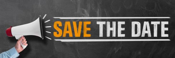 hand holding megaphone or bullhorn against blackboard with text save the date - приглашение стоковые фото и изображения
