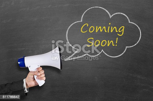 843847560 istock photo Hand holding megaphone with Coming Soon announcement 511786642