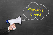 istock Hand holding megaphone with Coming Soon announcement 511786642
