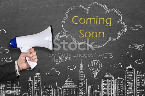 843847560 istock photo Hand holding megaphone with Coming Soon announcement 512045258
