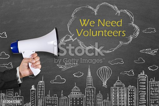 1155191162 istock photo Hand holding megaphone with We Need Volunteers on cityscape background 512041266