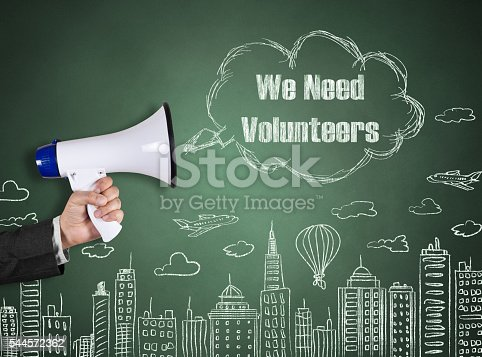 1155191162 istock photo Hand holding megaphone with We Need Volunteers on cityscape background 544572362