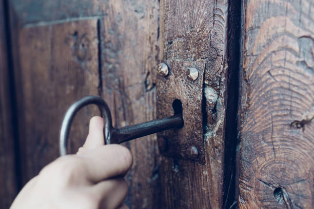 hand holding metal vintage key to unlocking old secret wooden door, film tone color - key stock pictures, royalty-free photos & images