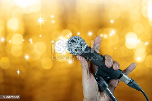 istock Hand holding microphone on stand with bokeh glow blurred background 628325438