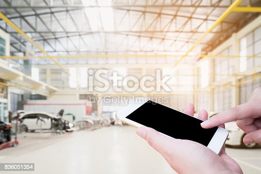 1073743202 istock photo hand holding mobile phone on car service centre 836051354