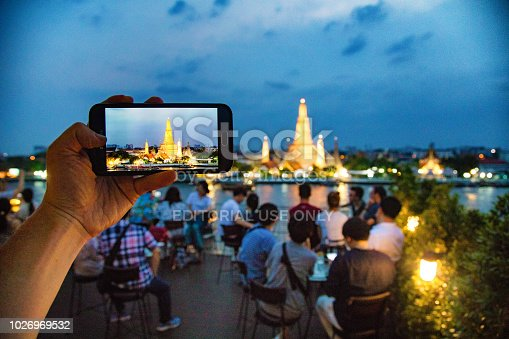 Hand holding mobile phone photographing Bangkok Wat Arun temple at dusk on a Sunny Winter day.