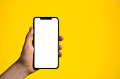 Hand holding mobile phone with blank white full screen on a yellow background