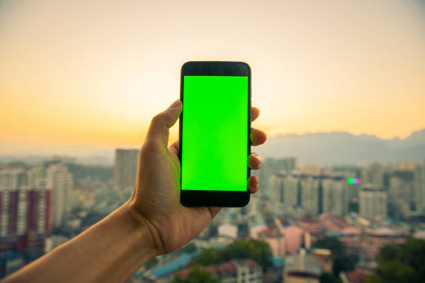 Hand holding mobile phone with chroma key screen stock photo