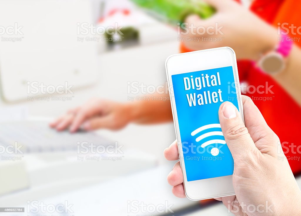 Hand holding mobile phone with digital wallet at supermarket blu stock photo