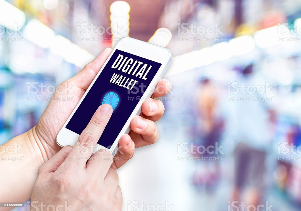 Hand holding mobile phone with Digital Wallet word with blurred stock photo