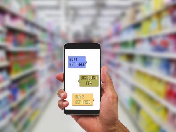 hand halten handy mit rabatt anmelden bildschirm einkauf im supermarkt - iphone gratis stock-fotos und bilder