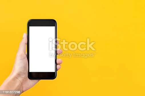 Hand holding empty screen mobile phone isolated on yellow background with copy space