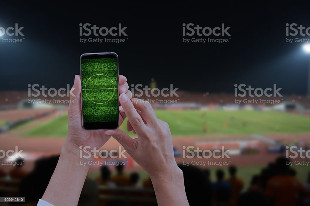 Hand holding mobile smart phone with football field, blurred soc stock photo
