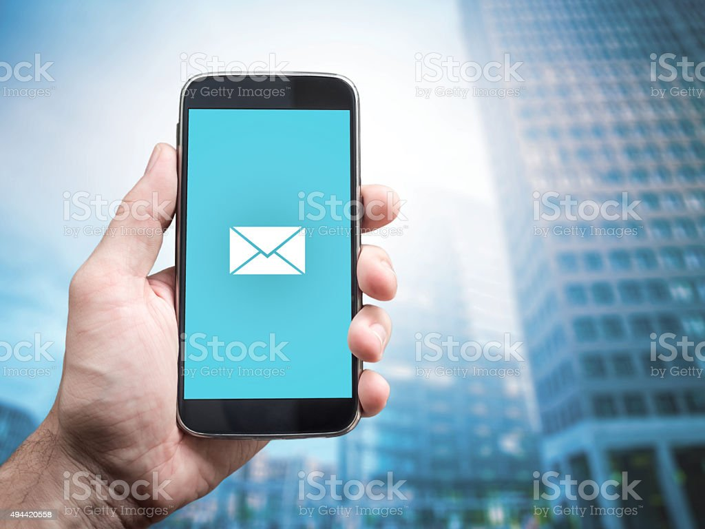 Hand holding mobile smart phone with message on a screen. stock photo