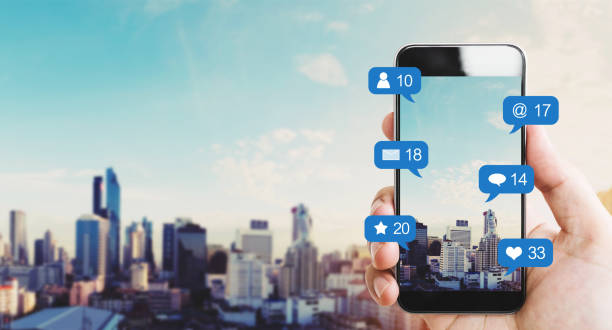 Hand holding mobile smart phone, with notification icons and city background stock photo