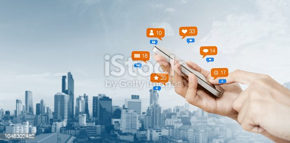 istock Hand holding mobile smart phone, with notification icons and city background 1046302482