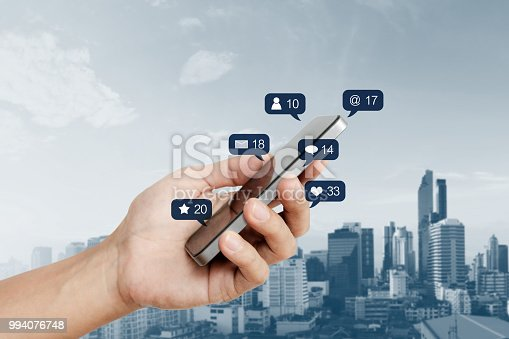 istock Hand holding mobile smart phone, with social media and social network notification icon 994076748