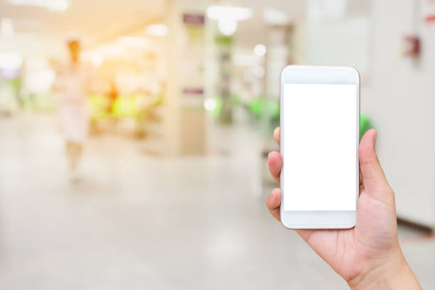 hand holding mobile smartphone with doctors and nurses in hospital stock photo