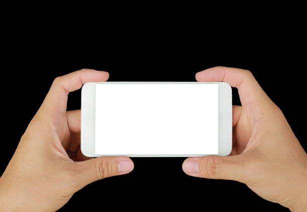 Hand holding mobile smartphone with white screen. Mobile photography concept. Isolated on black. stock photo