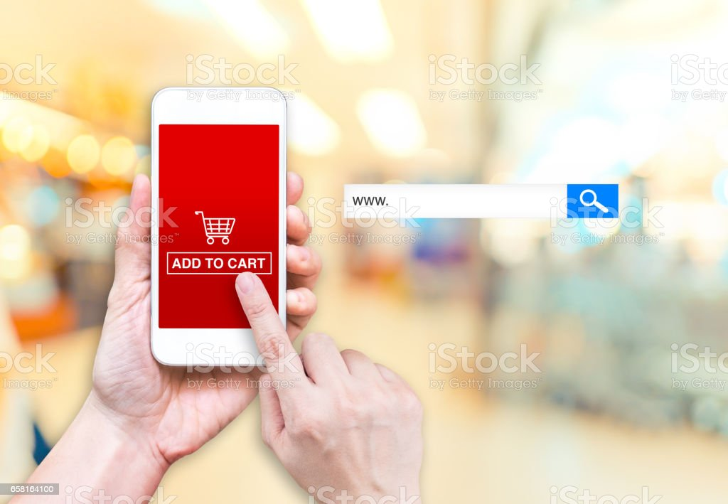 Hand holding mobile  with Add to cart button and empty screen for adding your design at blur store background bokeh light,Mock up for display of your shop name or logo,online shopping concept stock photo