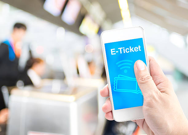 Hand holding mobile with E-Ticket with blur airport check-in bac stock photo