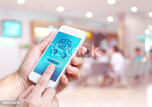 istock Hand holding mobile with Health check button and thumb up good or bad results at blur patient waiting for see doctor at Hospital hallway background bokeh light,Medicare concept 688033976