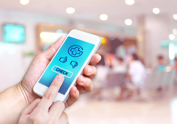 Hand holding mobile with Health check button and thumb up good or bad results at blur patient waiting for see doctor at Hospital hallway background bokeh light,Medicare concept stock photo