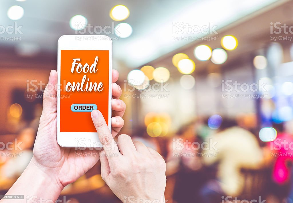 Hand holding mobile with Order food online with blur restaurant stock photo