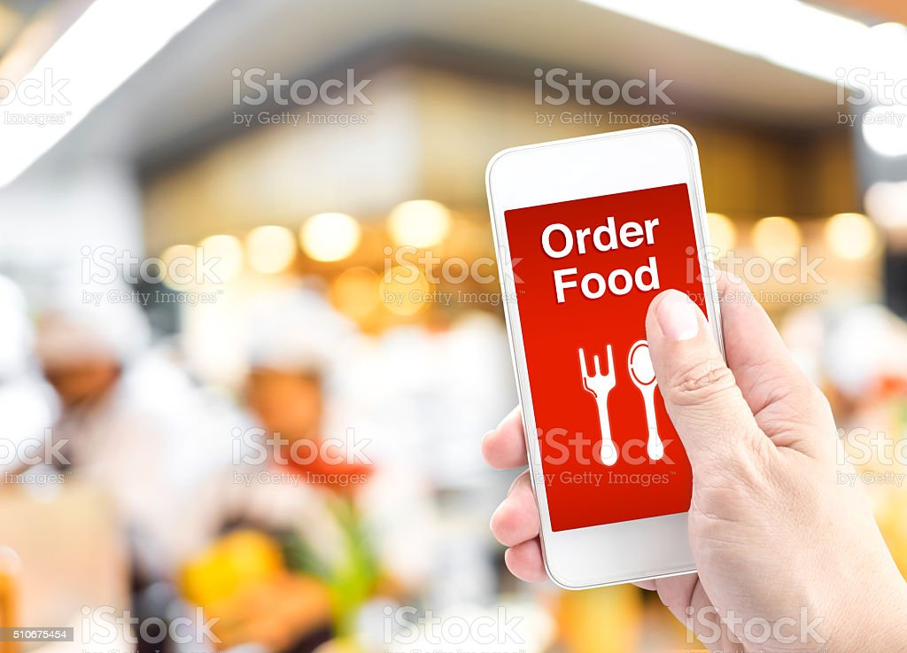 Hand holding mobile with Order food online with blur restaurant foto
