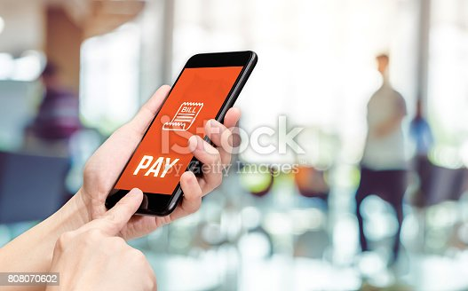 istock Hand holding mobile with pay word and bill icon feature with blur back office counter background,Digital Lifestyle concept 808070602