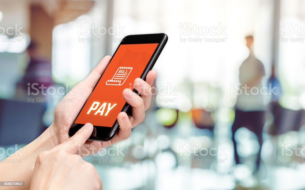 Hand holding mobile with pay word and bill icon feature with blur back office counter background,Digital Lifestyle concept stock photo