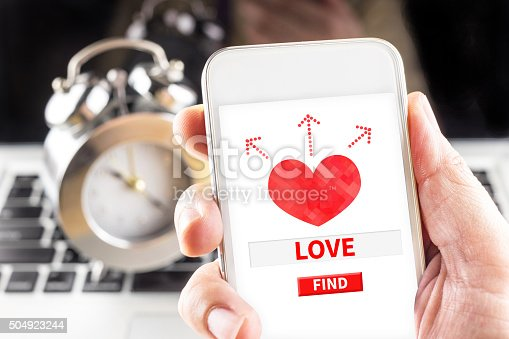 istock Hand holding mobile with red heart and find love 504923244