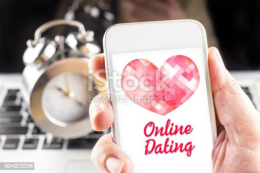 istock Hand holding mobile with red heart and online dating 504923208