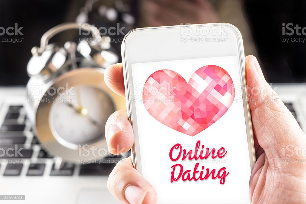 Hand holding mobile with red heart and online dating stock photo