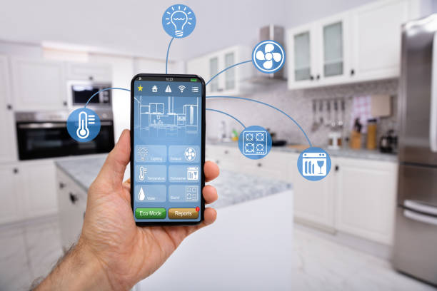 Hand Holding Mobile With Smart Home Control Icon Feature Close-up Of Man's Hand Holding Mobile With Smart Home Control Icon Feature With Kitchen Background smart thermostat stock pictures, royalty-free photos & images