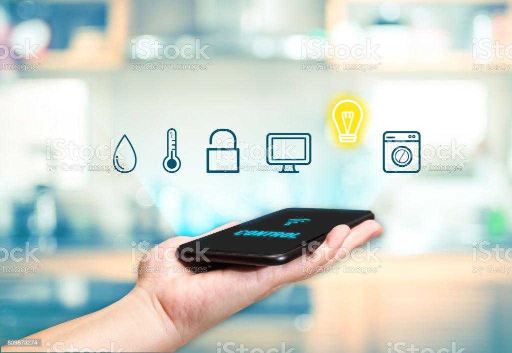 Handen håller mobil med funktionen Smart hem kontroll ikonen med oskärpa kök bakgrund, Digital Lifestyle konceptet bildbanksfoto
