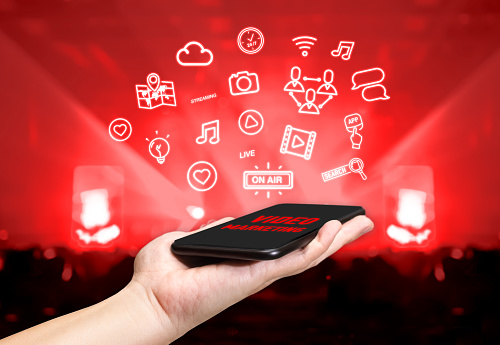 istock Hand holding mobile with Video marketing icon feature with blur live concert background,Digital Lifestyle concept 881687358