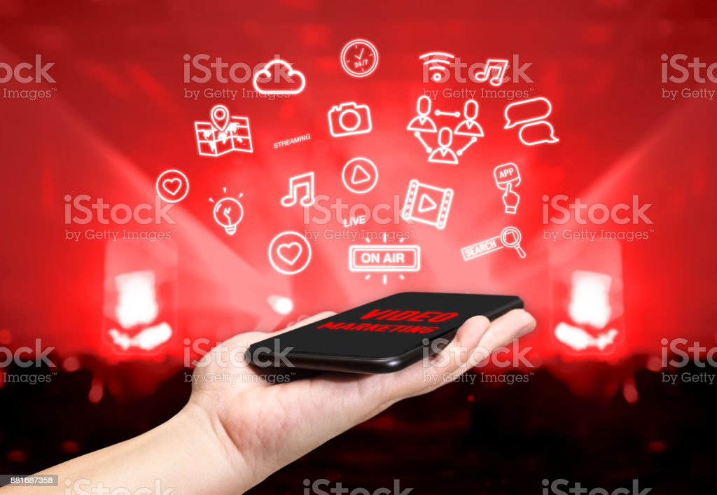 Hand holding mobile with Video marketing icon feature with blur live concert background,Digital Lifestyle concept stock photo