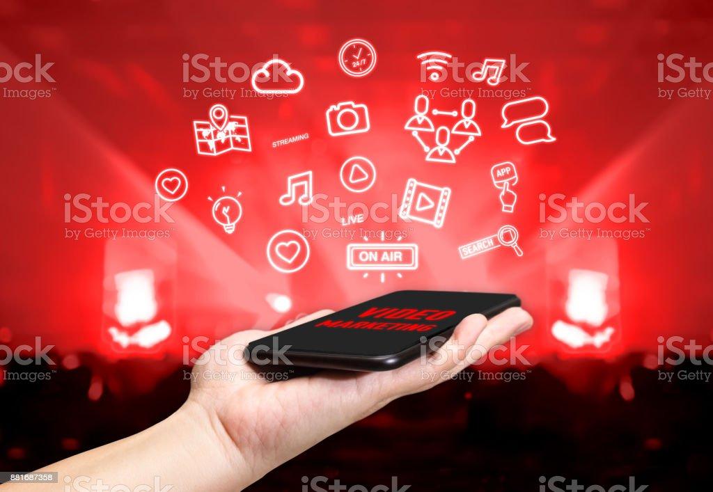 Mão segurando o celular com recurso de ícone marketing vídeo com fundo de concerto ao vivo do borrão, conceito de estilo de vida Digital - foto de acervo