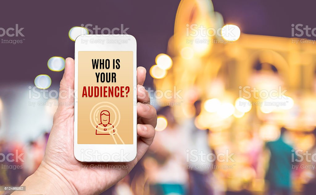 Hand holding mobile with Who is your audience? word stock photo