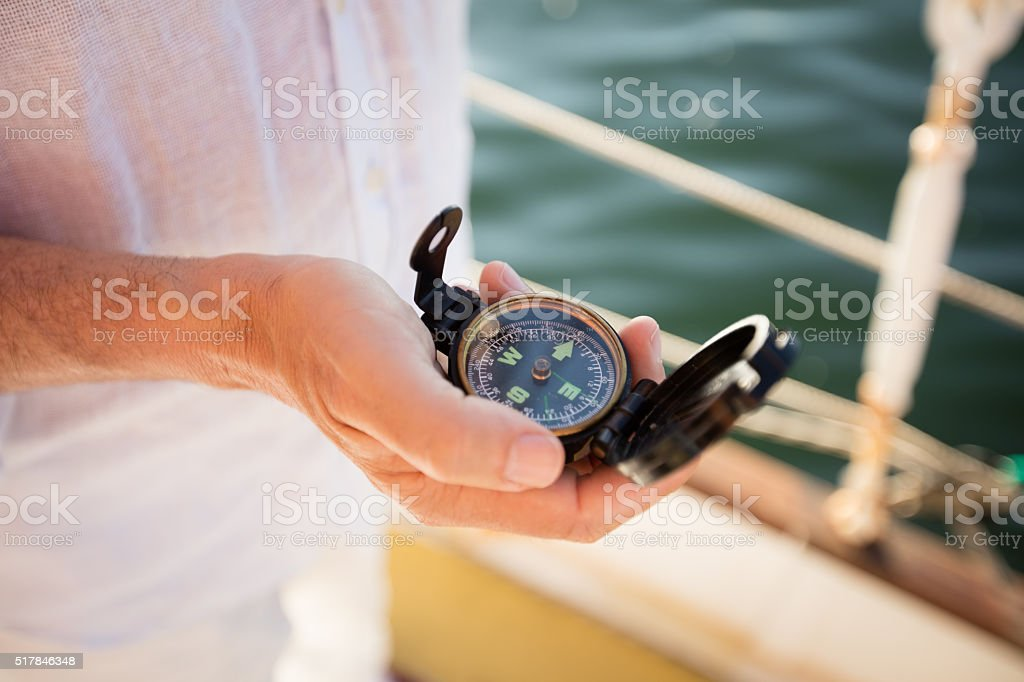 Hand holding modern compass with clear directions on a yacht stock photo