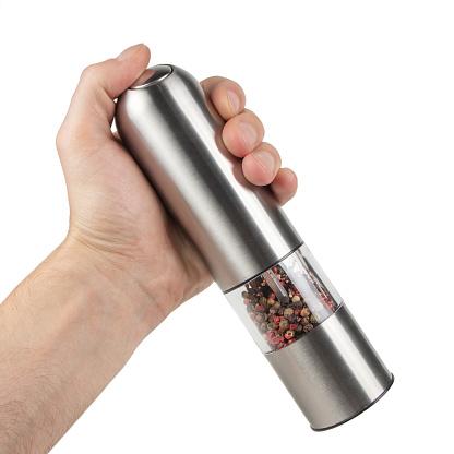 Hand holding modern silver pepper grinder.
