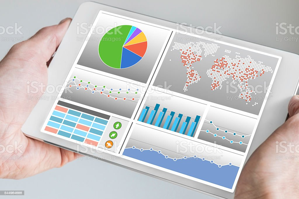 Hand holding modern tablet or mobile device with business dashboard stock photo