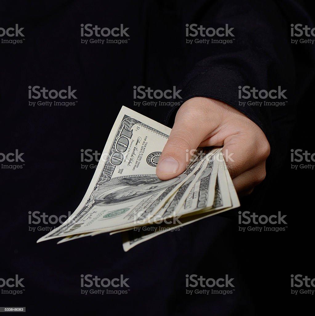 Hand holding money against dark background (concept of bribe/corruption) stock photo