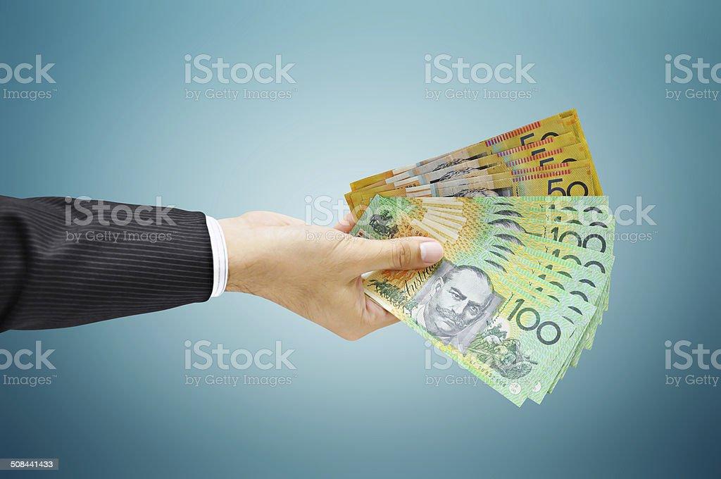 Hand holding money - Australian dollar (AUD) bills stock photo