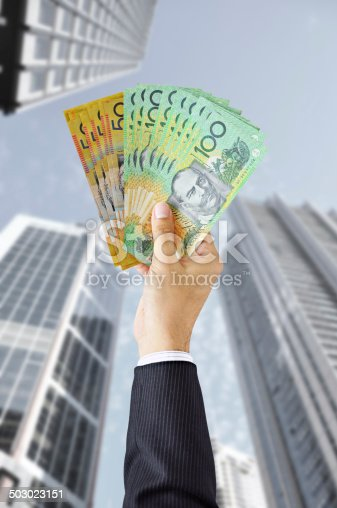 Hand holding money - Australian dollars (AUD) - on building background