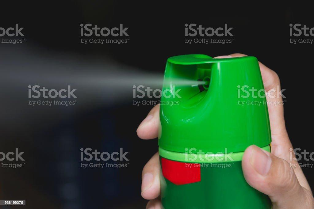 Hand mit Mückenspray. Menschen mit Mückenspray aus der Flasche. – Foto