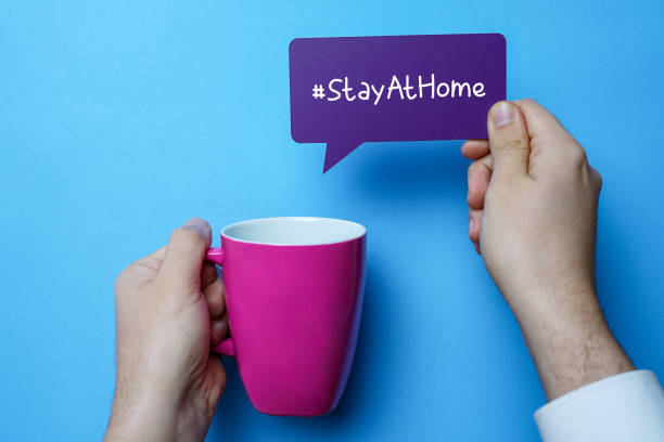 Hand holding mug and speech bubble with stay at home. stock photo