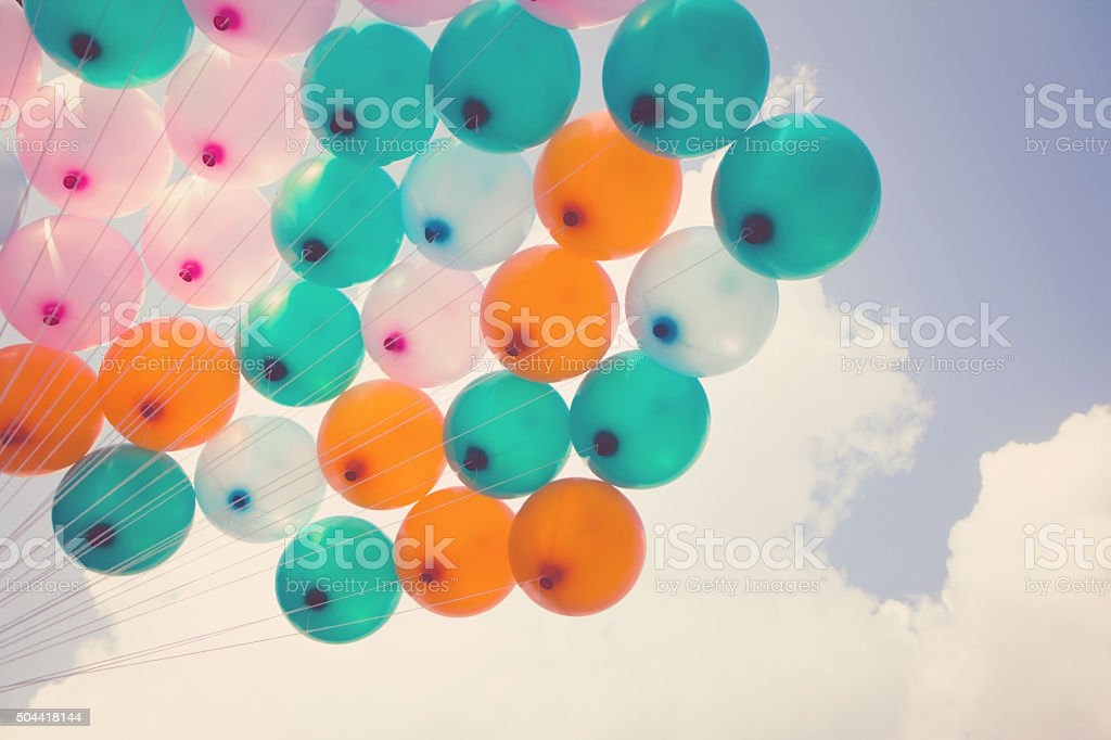 hand holding multicolored balloons. Vintage effect stock photo