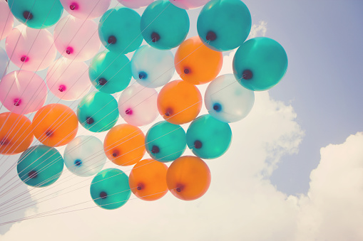 Hand Holding Multicolored Balloons Vintage Effect Stock Photo - Download Image Now